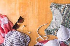 Vista superior de la ropa y de los accesorios del verano para la mujer en la tabla de madera Concepto de las vacaciones Fotografía de archivo libre de regalías