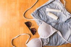 Vista superior de la ropa y de los accesorios del verano para la mujer en la tabla de madera Concepto de las vacaciones Imágenes de archivo libres de regalías
