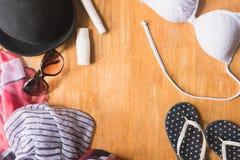 Vista superior de la ropa y de los accesorios del verano para la mujer en la tabla de madera Concepto de las vacaciones Fotos de archivo