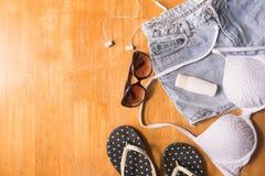 Vista superior de la ropa y de los accesorios del verano para la mujer en la tabla de madera Equipo de la playa del verano Concep Fotos de archivo libres de regalías