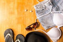 Vista superior de la ropa y de los accesorios del verano para la mujer en la tabla de madera Equipo de la playa del verano Concep Imagenes de archivo