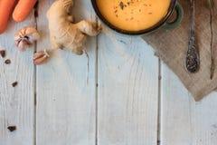 Vista superior de la sopa de la crema de la zanahoria del jengibre en la superficie blanca Imagen de archivo libre de regalías