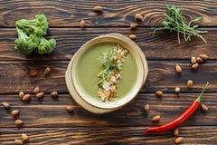 vista superior de la sopa poner crema vegetariana dispuesta, del bróculi fresco, de las almendras y de las pimientas de chile fotos de archivo