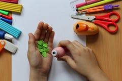 Vista superior de la tabla con una hoja de papel limpia y las manos de un bebé que hacen un regalo El día de madre y el día de la fotos de archivo