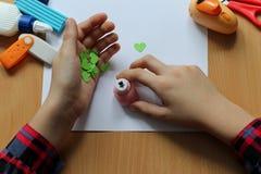 Vista superior de la tabla con una hoja de papel limpia y las manos de un bebé que hacen un regalo El día de madre y el día de la foto de archivo