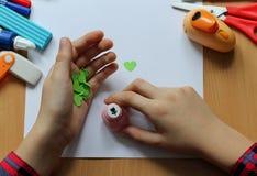 Vista superior de la tabla con una hoja de papel limpia y las manos de un bebé que hacen un regalo El día de madre y el día de la fotografía de archivo