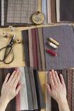 Vista superior de la tabla de costura con las telas, fuentes para la decoración casera o proyecto y mano del ` s de la mujer que  Imagen de archivo libre de regalías
