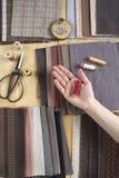 Vista superior de la tabla de costura con las telas, fuentes para la decoración casera o proyecto y mano del ` s de la mujer que  Imagen de archivo
