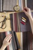 Vista superior de la tabla de costura con las telas, fuentes para la decoración casera o proyecto y mano del ` s de la mujer que  Imágenes de archivo libres de regalías