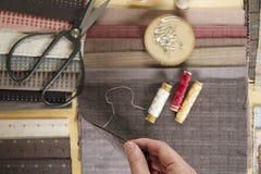 Vista superior de la tabla de costura con las telas, fuentes para la decoración casera o proyecto y mano del ` s de la mujer que  Fotografía de archivo