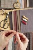 Vista superior de la tabla de costura con las telas, fuentes para la decoración casera o proyecto y mano del ` s de la mujer que  Fotos de archivo