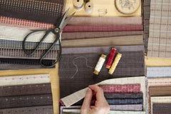 Vista superior de la tabla de costura con las telas, fuentes para la decoración casera o proyecto y mano del ` s de la mujer que  Fotos de archivo libres de regalías