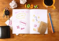 Vista superior de la tabla sucia con el cuaderno con garabatos, la taza de café, los papeles y las llaves Foto de archivo libre de regalías