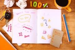Vista superior de la tabla sucia con el cuaderno con garabatos, la taza de café, los papeles y las llaves Foto de archivo