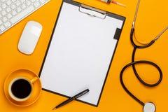 Vista superior de la tabla de un doctor con la libreta y estetoscopio de la pluma, teclado, prescripción y píldoras, una taza de  fotos de archivo