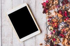 Vista superior de la tableta con las flores y las luces de la Navidad secadas en fondo de madera de la tabla Fotografía de archivo libre de regalías