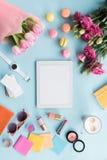 Vista superior de la tableta, de diversos accesorios, de macarons y de ramos de flores Imagen de archivo libre de regalías