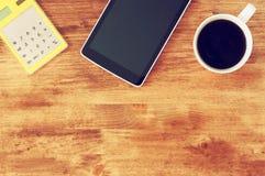 Vista superior de la tableta, de la taza de café y de la calculadora sobre fondo texturizado de madera de la tabla Fotos de archivo libres de regalías