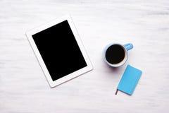 Vista superior de la tableta y de la taza de café en la tabla de madera foto de archivo