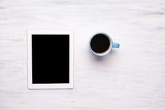 Vista superior de la tableta y de la taza de café en la tabla de madera Fotos de archivo libres de regalías