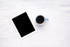 Vista superior de la tableta y de la taza de café en la tabla de madera foto de archivo libre de regalías