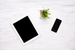 Vista superior de la tableta y del smartphone en la tabla de madera imagen de archivo