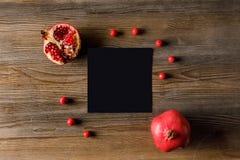 vista superior de la tarjeta vacía negra con las granadas Imagen de archivo libre de regalías
