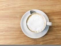 Vista superior de la taza blanca de café caliente en la tabla enselvada con la cuchara Fotografía de archivo libre de regalías