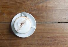 Vista superior de la taza de café caliente en la tabla de madera Imagen de archivo libre de regalías