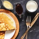 Vista superior de las crepes rusas del plato, de la leche, del atasco, del chocolate blanco, de la toalla, del potholder, del cuc imagen de archivo