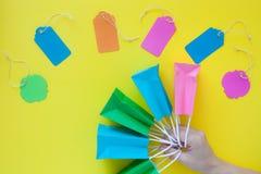 Vista superior de las etiquetas coloridas y de la mano de la venta que llevan a cabo pequeño p que hace compras Imágenes de archivo libres de regalías