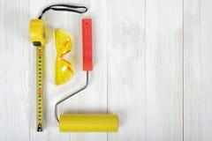 Vista superior de las herramientas de la construcción en el banco de trabajo de madera de DIY Cinta métrica, vidrios y rodillo de Fotografía de archivo libre de regalías