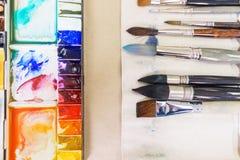 Vista superior de las herramientas del ` s del artista mientras que trabaja con la pintura de la acuarela Fotos de archivo libres de regalías