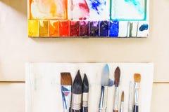 Vista superior de las herramientas del ` s del artista mientras que trabaja con la pintura de la acuarela Imagen de archivo