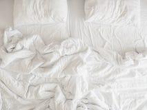 Vista superior de las hojas y de la almohada sin hacer, cama sucia sin hacer del lecho después del concepto del sueño de la comod imagenes de archivo