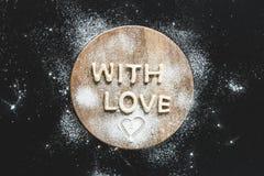 Vista superior de las letras comestibles con amor de la pasta en tabla de cortar de madera Fotos de archivo libres de regalías