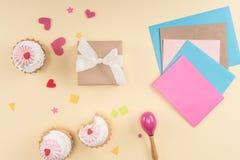 Vista superior de las letras del feliz cumpleaños, de las tortas, de los sobres y de la caja de regalo en beige Imágenes de archivo libres de regalías
