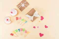 Vista superior de las letras del feliz cumpleaños, de los sobres con las cintas y de los símbolos de los corazones en rosa Imagen de archivo libre de regalías