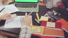 Vista superior de las manos del diseñador que cambia formato los datos sobre la ubicación de los muebles en el nuevo apartamento metrajes