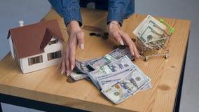 Vista superior de las manos femeninas jovenes que ponen el dinero en la tabla almacen de metraje de vídeo