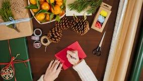 Vista superior de las manos que ponen una postal en sobre y que escriben saludos de la Navidad almacen de metraje de vídeo