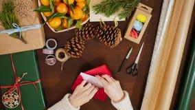 Vista superior de las manos que ponen una postal en sobre y que escriben saludos de la Navidad Imagen de archivo libre de regalías