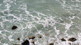 Vista superior de las ondas del mar que golpean la orilla de la roca Inclinación del movimiento de la cámara metrajes