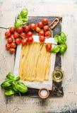 Vista superior de las pastas del Fettuccine con los tomates, las hojas de la albahaca y el aceite de oliva en fondo rústico Imágenes de archivo libres de regalías