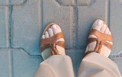Vista superior de las piernas de la mujer en sandalias, del concepto de viaje y del turismo Fotografía de archivo libre de regalías