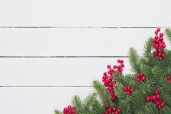 Vista superior de las ramas de la picea, de los conos del pino, de las bayas rojas y de la campana en el fondo de madera blanco d foto de archivo libre de regalías