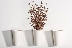 Vista superior de las tazas de papel disponibles blancas con los granos de café Fotos de archivo