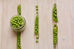 Vista superior de las vainas de guisante y de las semillas de guisante frescas, dulces, partidas en botella en fondo de madera Imagen de archivo libre de regalías