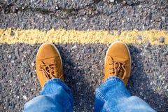 Vista superior de las zapatillas de deporte masculinas en la carretera de asfalto Foto de archivo libre de regalías