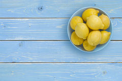 Vista superior de limones en la placa azul sobre fondo tropical Fotos de archivo